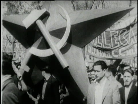 Demonstrators carry a large hammer and sickle statue an image of Joseph Stalin covers the side of a truck