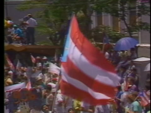 demonstrators carrying u.s. and puerto rican flags march down a wide street during a rally in puerto rico in 1989. - puerto rican ethnicity stock videos & royalty-free footage