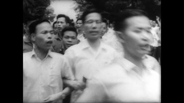 stockvideo's en b-roll-footage met demonstrators chant outside gates of british government house / paste protest posters to walls / protestors talk to the streets / crowd throws rocks... - 1967