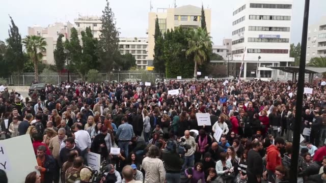 demonstrators gather during a protest by bank workers outside the cypriot central bank in nicosia cyprus demonstrators shout and wave placards and... - キプロス ニコシア点の映像素材/bロール