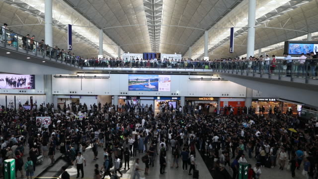 demonstrators gather in the arrival hall during a protest at the hong kong international airport in hong kong, china, on friday, july 26, 2019. - hong kong international airport stock videos & royalty-free footage