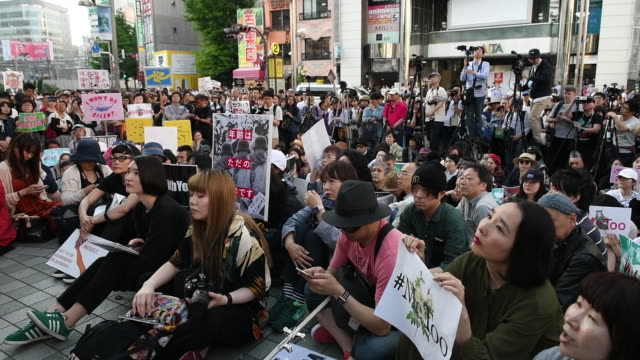 demonstrators hold signs and listen to a speech during a rally against sexual harassment in the shinjuku district of tokyo japan on saturday april 28... - social movement stock videos & royalty-free footage