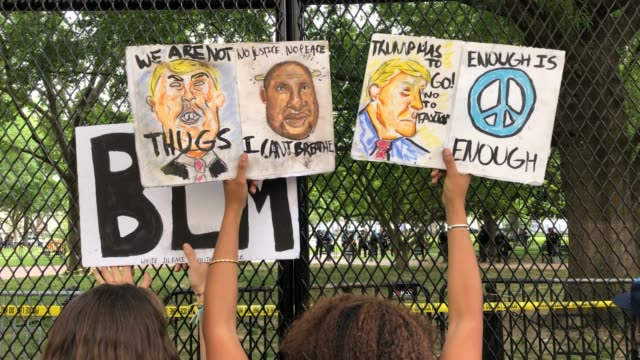 vidéos et rushes de demonstrators hold signs with the likeness of president donald trump george floyd and 'blm' for 'black lives matter' while chanting behind the new... - clôture