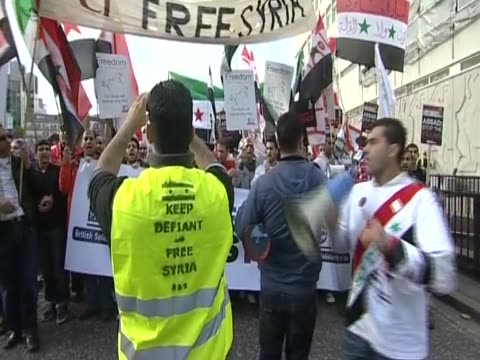 demonstrators march in london against the syrian assad government - syrien stock-videos und b-roll-filmmaterial