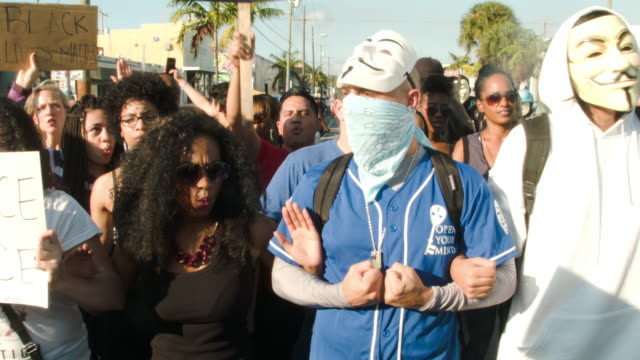 vidéos et rushes de demonstrators march through the wynwood neighborhood and along interstate 195 to protest police abuse on december 7, 2014 in miami, florida. the... - visage caché