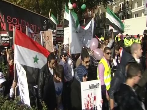 demonstrators march to the syrian embassy in london to protest against the assad government - demonstrant stock-videos und b-roll-filmmaterial