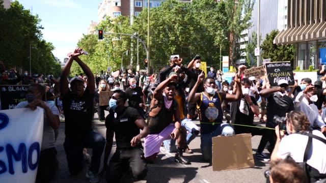 vídeos y material grabado en eventos de stock de demonstrators shout slogans during a black lives matter protest following the death of george floyd as a banner reads 'stop racism' outside the... - racismo