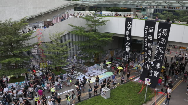 demonstrators stand in front of a statue of queen victoria during a protest in the causeway bay district of hong kong, china, on saturday, sept. 28,... - occupy protests stock videos & royalty-free footage