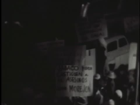 vídeos y material grabado en eventos de stock de demonstrators supporting the cuban revolutionary regime carry signs in front of a hotel. - 1950 1959