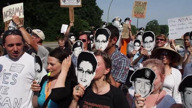Demonstrators wearing masks depicting Bradley Manning and Edward Snowden Protest Prism Spy Software During the President Barack Obama Visit on June...