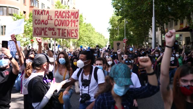 vídeos y material grabado en eventos de stock de demonstrators with raised fists and kneeling hold placards that read 'racism is like the covid 19 assume you have it' during a black lives matter... - racismo