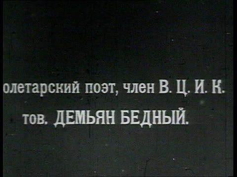 vidéos et rushes de demyan bedny poet stands in bolshevik uniform in front of train smokes cigarette / russia - 1918