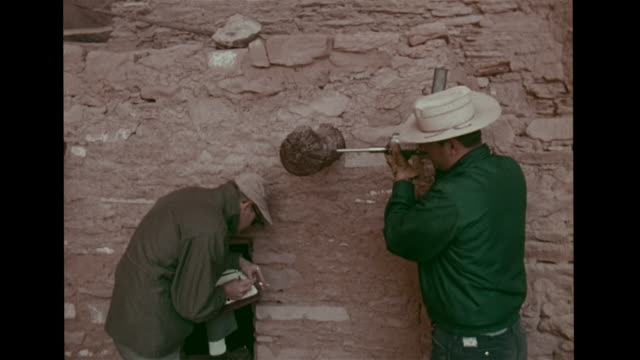 VS Dendrochronologists Bryant Bannister Jeffrey S Dean working at Keet Seel cliff dwellings ruins Navajo National Monument drilling taking core...