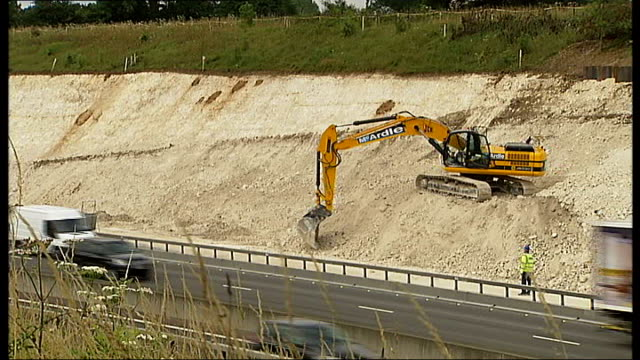 vídeos de stock e filmes b-roll de reporter to camera high angle shot of widening work underway beside motorway at bridge area high angle shot of earthmover at work as traffic along on... - cargo governamental