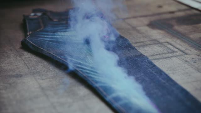 vidéos et rushes de gravure laser denim jeans. fabrication de denim. déchirer jeans avec une machine laser à l'usine de vêtements. fabrication de vêtements. - denim