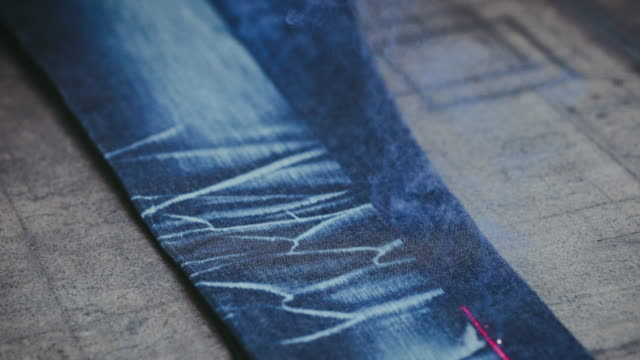 vídeos de stock e filmes b-roll de denim jeans laser engraving. manufacturing denim. ripping jeans with a laser machine at clothing factory. garment manufacturing. - jeans