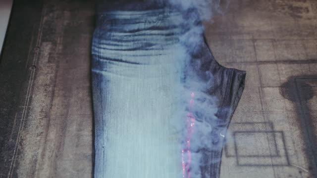 denim jeans laser gravur. herstellung denim. ripping jeans mit einer lasermaschine in der bekleidungsfabrik. bekleidungsherstellung. - maßkonfektion stock-videos und b-roll-filmmaterial