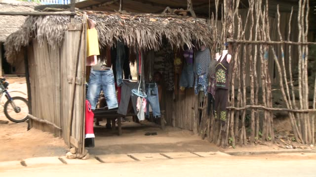 denim shorts hang in the storefront of a grass hut in madagascar. available in hd. - grass hut stock videos & royalty-free footage