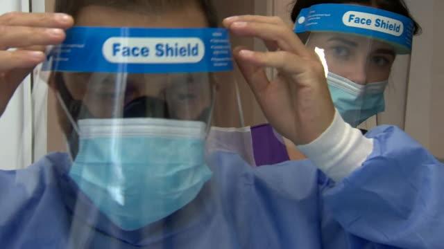 denist putting on ppe as dental practice in essex reopens during coronavirus pandemic - dental hygiene stock videos & royalty-free footage