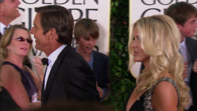 Dennis Quaid waves and smiles as he walks w/ wife Kimberly Quaid down the red carpet at the Beverly Hilton Hotel