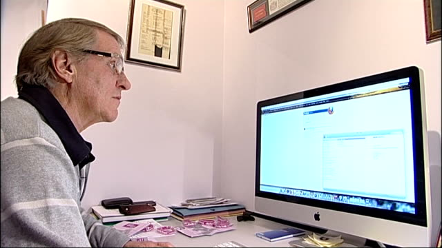 Denny Wise sitting at widescreen Apple Mac computer Close shot of 'Forces Children Trust' booklet PAN