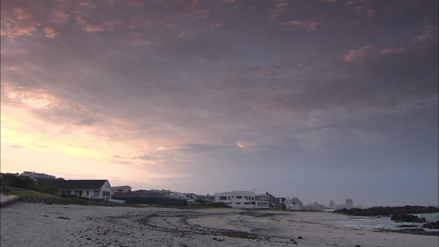 A dense cloud layer hangs over oceanfront homes on a sandy beach on Cape Peninsula.