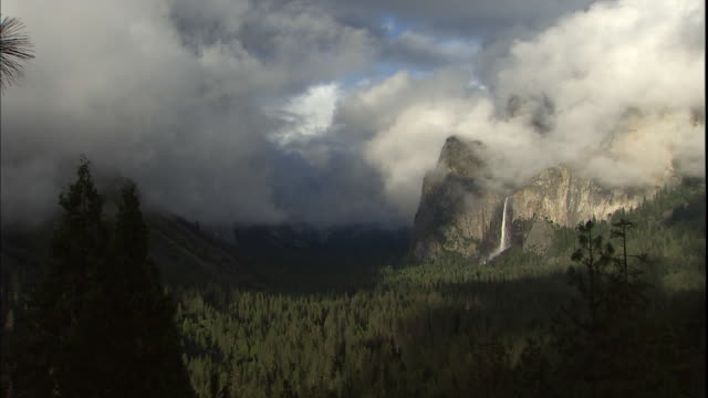 Dense clouds and fog hover near Bridalveil Falls in the Yosemite Valley.