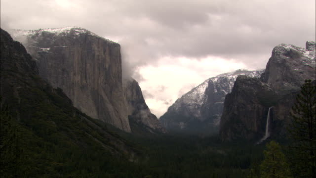 dense clouds form over the tops of craggy mountains in yosemite national park. - エルキャピタン点の映像素材/bロール