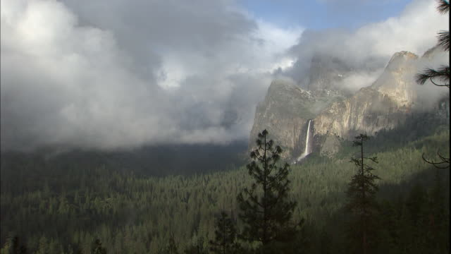 Dense clouds hover near Bridalveil Falls in the Yosemite Valley.