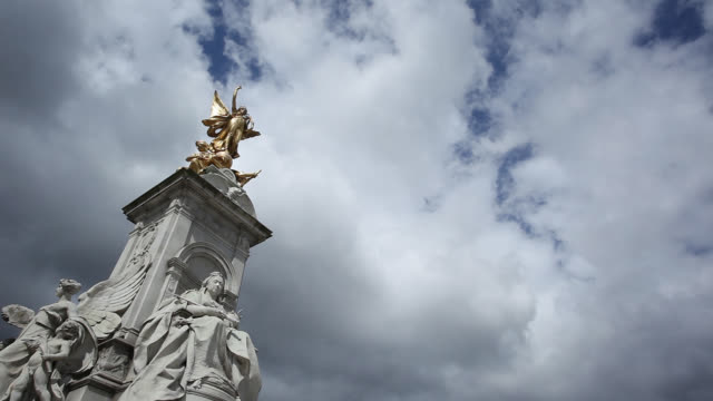 dense clouds loom above the queen victoria memorial statue in front of buckingham palace. - バッキンガム宮殿点の映像素材/bロール