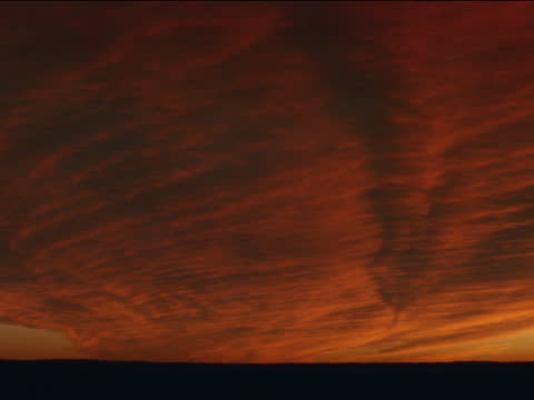 dense  clouds reflect red and orange light over a dark horizon. - red tape stock videos & royalty-free footage