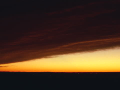 dense clouds reflect red light in a bright yellow sky. - red tape stock videos & royalty-free footage