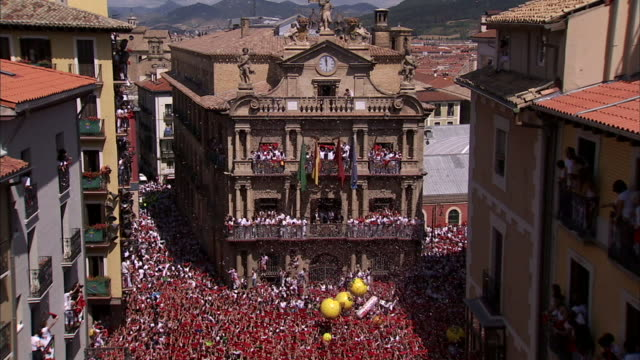 dense crowd of thousands of unidentifiable people holding up red neckties flags beach balls inflatable cones bouncing around as confetti falls in... - comunidad foral de navarra stock videos and b-roll footage