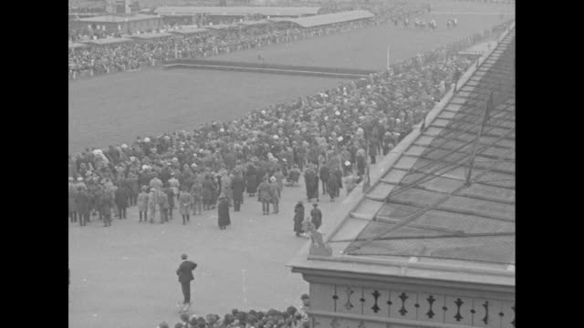 dense crowds enter auteuil hippodrome / jockeys parade horses with crowds on both sides of track prior to start of the grand steeplechase de paris /... - hurdling horse racing stock videos and b-roll footage