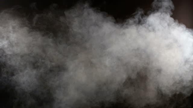 dicht flaumig puffs von weißer rauch und nebel auf schwarzem hintergrund, abstrakt rauchwolke - transparent stock-videos und b-roll-filmmaterial