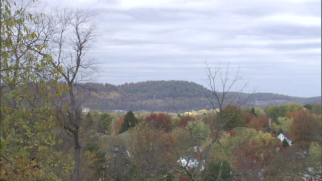 a dense forest in autumn leaves obscures morgantown, west virginia except for a few buildings and a steeple. - steeple stock videos & royalty-free footage