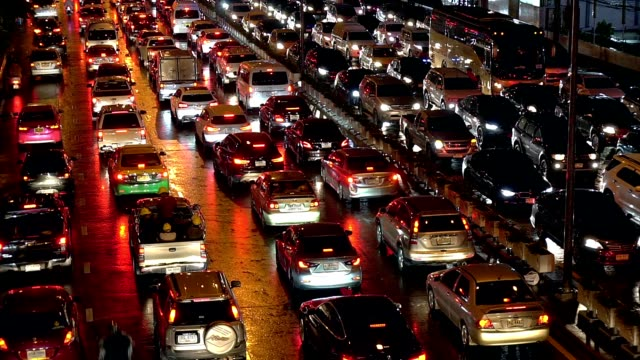 dense night traffic jam of phet phra ram road at rainy night in bangkok thailand. - ingorgo stradale video stock e b–roll