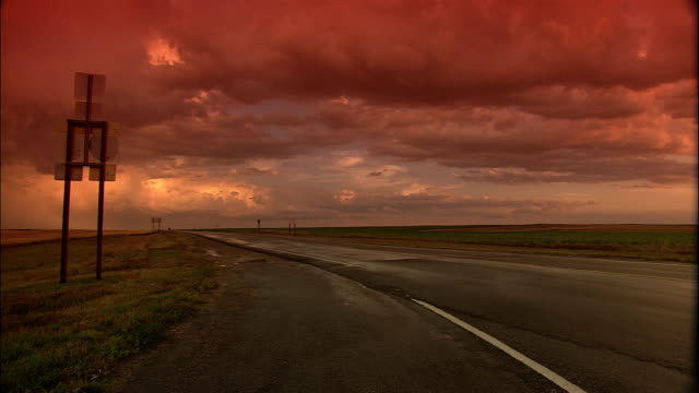 dense pastel clouds at sunset fill the sky over an empty rural highway. - empty road stock videos & royalty-free footage