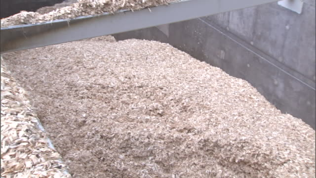 dense piles of woodchips and shavings fill a vat at a paper mill. - paper mill stock videos & royalty-free footage