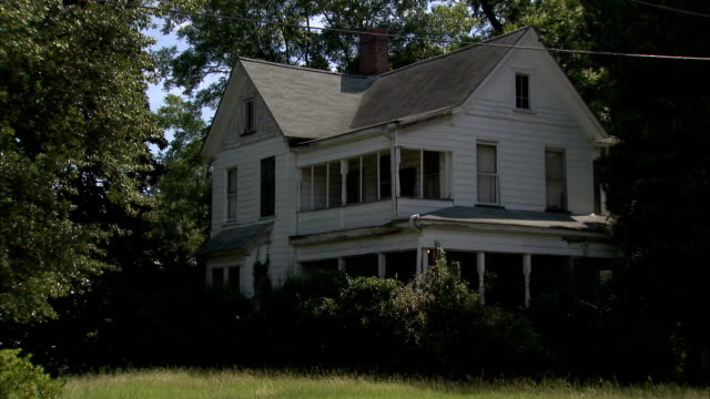 vídeos de stock e filmes b-roll de dense trees and bushes surround an abandoned, two-story house in south carolina. available in hd. - descuidado