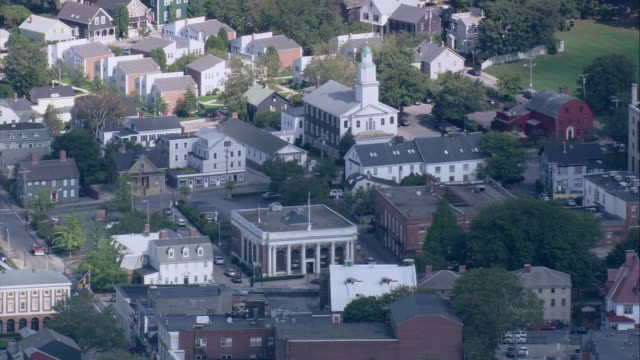 vídeos y material grabado en eventos de stock de aerial densely populated easton's point neighborhood with a church and white steeple, and newport harbor and goat island / newport, rhode island, united states - formato buzón