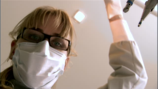 vídeos de stock, filmes e b-roll de dental assistant adjusts overhead light - dentista