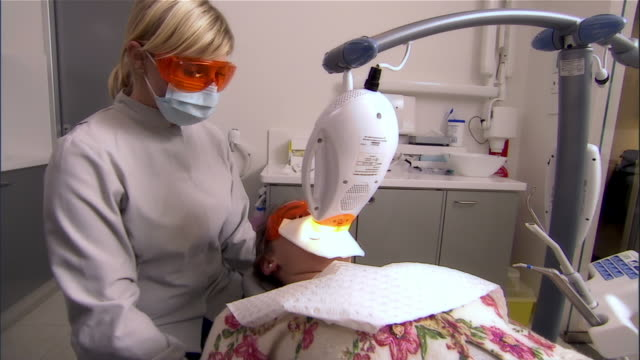 dental assistant looks on as woman undergoes high-intensit - ガーゼ点の映像素材/bロール