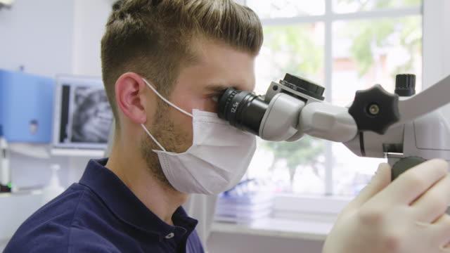 tand-medarbetare som undersöker på sjukhus - kirurgmask bildbanksvideor och videomaterial från bakom kulisserna