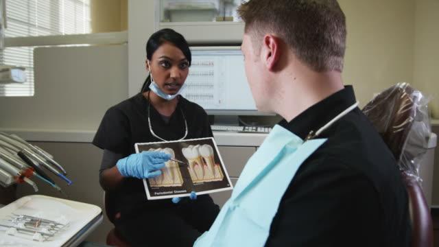 dental hygienist explaining dental care to a man - three quarter length stock videos & royalty-free footage