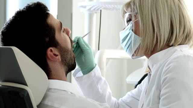 vídeos de stock e filmes b-roll de procedimento de dentista - dentista