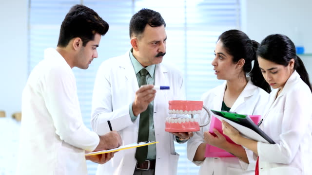 ms dental professor explaining students about teeth model in laboratory / delhi, india - giacca e cravatta video stock e b–roll