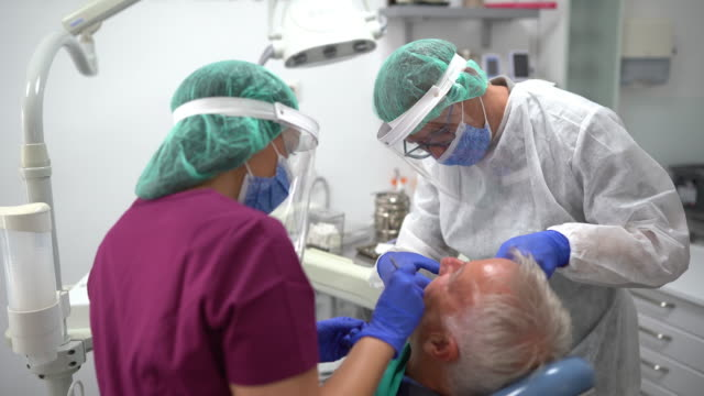dental team performing dental procedure at dentist's office - dental hygiene stock videos & royalty-free footage