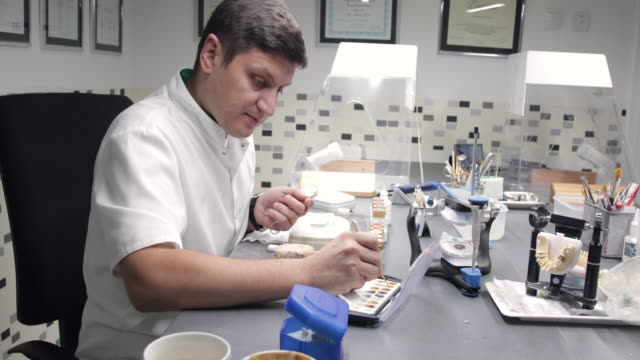 dental technician colouring veneers with spatula - veneers stock videos and b-roll footage