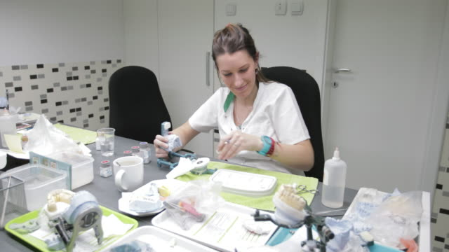 dental technician filling dental bridge with plaster - tooth cap stock videos and b-roll footage